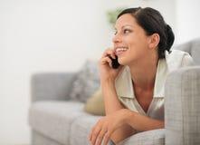 Donna che pone sul sofà e sul cellulare parlante Fotografia Stock Libera da Diritti