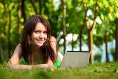 Donna che pone sull'erba con il computer portatile Fotografia Stock