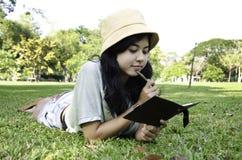 Donna che pone sull'erba e che pensa nella sosta Fotografie Stock