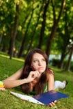 Donna che pone sull'erba e sul pensiero Immagini Stock Libere da Diritti