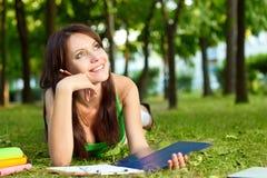 Donna che pone sull'erba e sul sogno Fotografie Stock