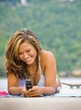 Donna che pone sull'invio di messaggi di testo del pilastro fotografie stock