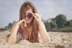 Donna che pone sulla sabbia immagine stock