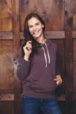 Donna che porta maglietta felpata magenta davanti alla parete di legno Fotografia Stock