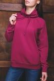 Donna che porta maglietta felpata magenta davanti alla parete di legno Fotografie Stock Libere da Diritti