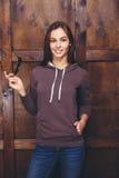 Donna che porta maglietta felpata magenta davanti alla parete di legno Fotografia Stock Libera da Diritti