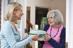 Donna che porta pasto per il vicino anziano Fotografie Stock