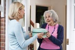 Donna che porta pasto per il vicino anziano Immagini Stock Libere da Diritti