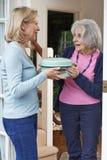 Donna che porta pasto per il vicino anziano Fotografia Stock