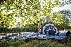 Donna che porta un cappello di paglia in natura di estate che legge un libro Fotografie Stock Libere da Diritti