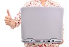 Donna che porta un computer portatile e che mostra i pollici su, isolato su bianco Fotografia Stock