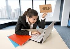 Donna che porta un vestito che lavora al suo computer portatile che tiene un segno di aiuto che si siede all'ufficio moderno fotografia stock libera da diritti