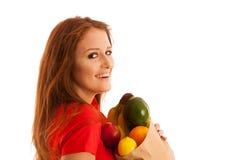 Donna che porta una borsa in pieno di vari frutti isolati sopra bianco Immagini Stock Libere da Diritti