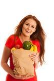 Donna che porta una borsa in pieno di vari frutti isolati sopra bianco Fotografia Stock Libera da Diritti