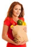 Donna che porta una borsa in pieno di vari frutti isolati sopra bianco Fotografie Stock Libere da Diritti