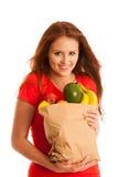 Donna che porta una borsa in pieno di vari frutti isolati sopra bianco Immagine Stock Libera da Diritti