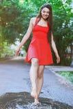 Donna che porta vestito rosso che salta in una pozza dopo la pioggia Fotografia Stock