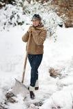 Donna che posa con la pala della neve Fotografia Stock
