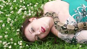 Donna che posa con un serpente intorno al suo collo stock footage