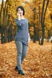 Donna che posa nel parco con gli alberi gialli, stagione di autunno di caduta Fotografia Stock