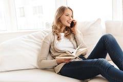 Donna che posa seduta all'interno a casa che parla dal telefono cellulare fotografie stock