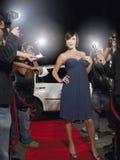 Donna che posa sul tappeto rosso che è fotografato dai paparazzi Immagini Stock