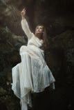 Donna che posa sulle rocce della foresta Fotografie Stock