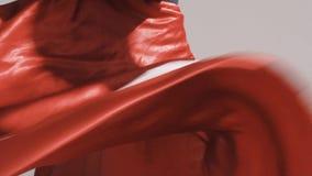 Donna che posa in una gonna rossa d'ondeggiamento Ondeggiamento rosso del panno video d archivio
