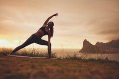 Donna che pratica asana di yoga di Utthita Parsvakonasana Fotografia Stock Libera da Diritti