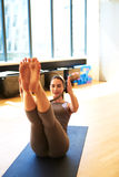 Donna che pratica Pilates sulla stuoia del pavimento in studio Immagine Stock Libera da Diritti