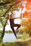 Donna che pratica yoga antigravità all'albero vicino al fiume Immagini Stock Libere da Diritti