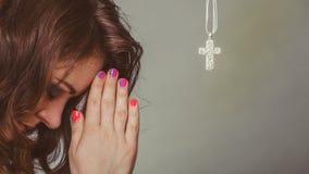 Donna che prega al dio Gesù con la collana trasversale fotografie stock
