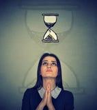 Donna che prega cercando l'orologio della sabbia fatto pressione su da mancanza di tempo Fotografie Stock Libere da Diritti