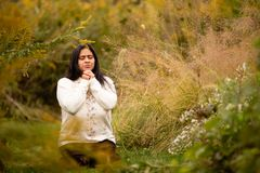 Donna che prega in Forest Preserve Alone su bello Autumn Day immagine stock