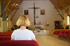 Donna che prega nella chiesa Immagini Stock