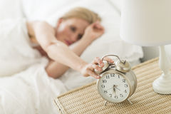 Donna che preme bottone della sveglia sul comodino Immagini Stock Libere da Diritti