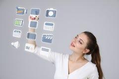 Donna che preme le multimedia e le icone di spettacolo su un fondo virtuale Fotografie Stock Libere da Diritti