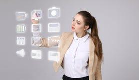 Donna che preme le multimedia e le icone di spettacolo su un fondo virtuale Fotografia Stock Libera da Diritti