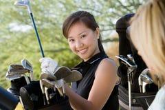 Donna che prende club di golf Immagini Stock Libere da Diritti