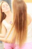 Donna che prende cura dei suoi capelli lunghi che applicano olio cosmetico Immagini Stock