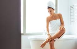 Donna che prende cura del suo corpo dopo il bagno fotografia stock