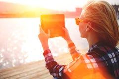 Donna che prende foto con la macchina fotografica del cuscinetto di tocco mentre sedendosi su un molo del fiume durante il tempo  Fotografia Stock Libera da Diritti
