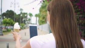 Donna che prende foto del cono gelato Il gelato fotografante teenager sulla macchina fotografica telefona al rallentatore video d archivio