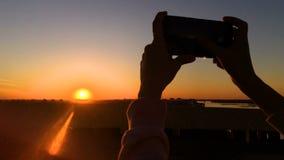 Donna che prende foto del tramonto con lo smartphone in citt? stock footage