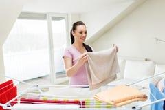 Donna che prende gli asciugamani di bagno dallo stendipanni a casa Fotografia Stock