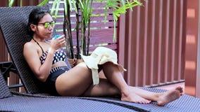 Donna che prende il sole su una sedia archivi video