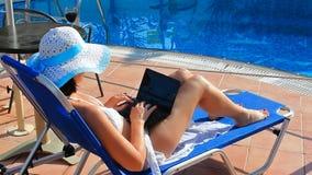 Donna che prende il sole sulla sedia a sdraio con il computer portatile stock footage