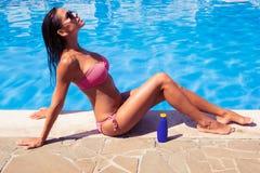 Donna che prende il sole vicino allo stagno di nuotata Immagini Stock Libere da Diritti