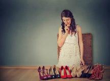 Donna che prende le decisioni che selezionano le giuste paia delle scarpe del tacco alto Immagine Stock