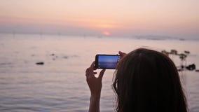 Donna che prende le immagini con il suo smartphone al bello tramonto sulla spiaggia vicino al mare sulla vacanza Movimento lento archivi video